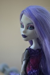 Close-up portrait of a human figurine with purple hair looking away