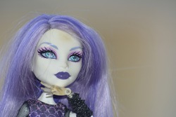 Close-up portrait of a human figurine with purple hair posing for the camera