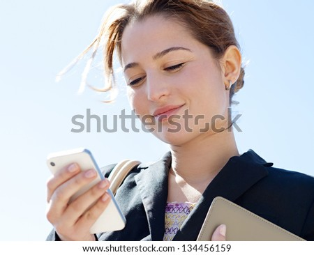 Close up portrait of a joyful businesswoman using her smartphone and carrying work folders, standing against a sunny blue sky.