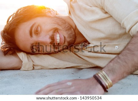 Close up portrait of a joyful young attractive man lying down and relaxing on a white sand beach with the sunset behind him with flare and warm flooding light on vacation, smiling.