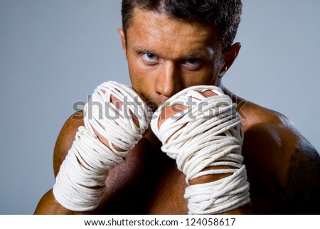 Close-up portrait of a kick-boxer in a fighting stance. Kickboxing or muay thai