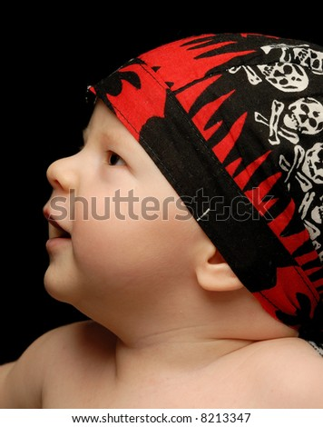 Close-up portrait of a little baby in sculled bandanna looking up