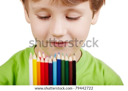 Close-up portrait  of a little boy in the green t-shirt who examines colour pencils - stock photo