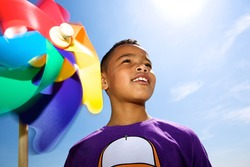 Close up portrait of a little boy smiling outdoors with colorful windmill