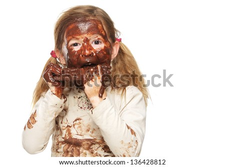 Close up portrait of a little girl eating chocolate bar and face covered in chocolate isolated on white