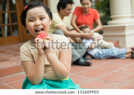 Close-up portrait of a little girl eating tasty watermelon on the foreground