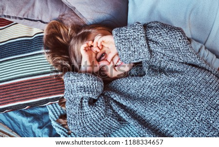 Close-up portrait of a little girl in warm sweater lying on bed. #1188334657