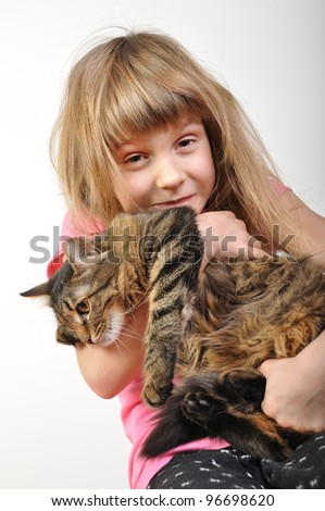 close-up portrait of a little girl playing with acat