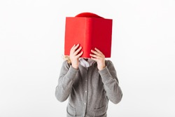 Close up portrait of a little schoolgirl dressed in uniform covering face with a book isolated over white background
