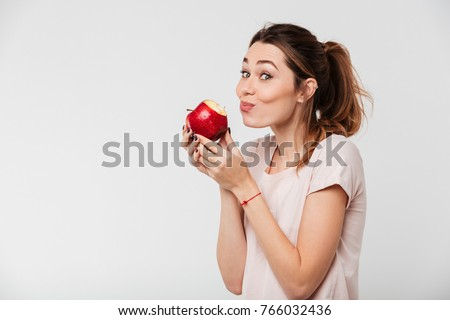 Close up portrait of a lovely pretty girl biting an apple isolated over white background