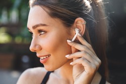 Close up portrait of a lovely young fitness girl listening to music through wireless earphones outdoors