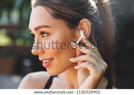 Close up portrait of a lovely young fitness girl listening to music through wireless earphones outdoors #1130328905
