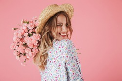 Close up portrait of a lovely young woman in summer dress and straw hat holding carnations bouquet and looking over her shoulder isolated over pink background