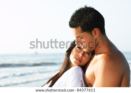 close up portrait of a  loving couple looking at the horizon from the shore of the beach