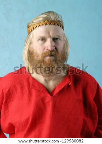 close-up portrait of a man with a red beard and mustache, long blond hair on a light background