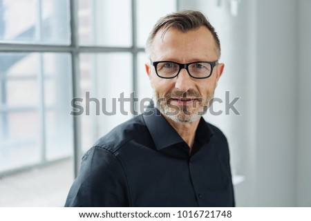 Close-up portrait of a middle-aged man wearing black shirt and eyeglasses while looking at camera with confidence in the office
