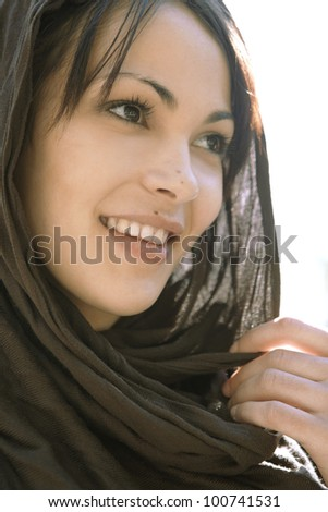Close up portrait of a muslim woman wearing a head scarf, smiling.