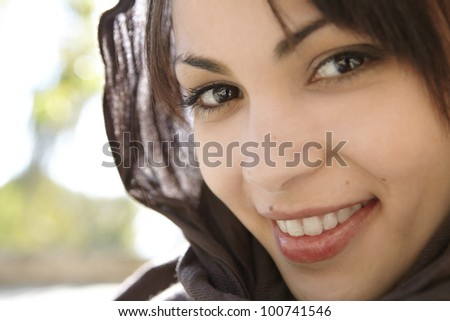 Close up portrait of a muslim woman wearing a head scarf smiling at camera.