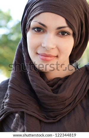 Close up portrait of a muslim young woman wearing a head scarf and smiling at the camera, outdoors.