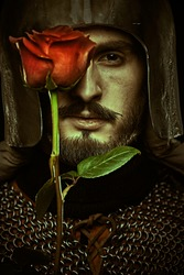 Close-up portrait of a noble knight in armor with a red rose in his hands. The era of romanticism.