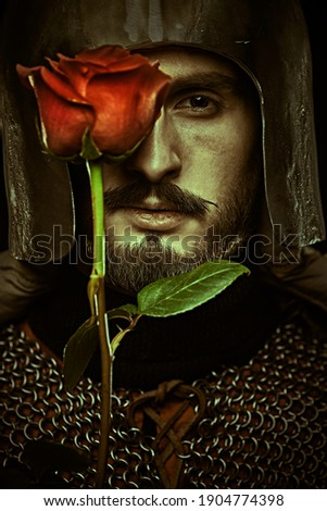 Close-up portrait of a noble knight in armor with a red rose in his hands. The era of romanticism.  Stok fotoğraf ©