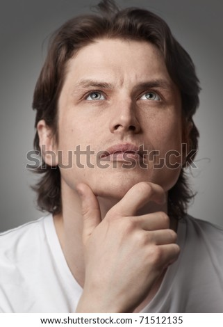 Close-up portrait of a pensive handsome man looking up against white background