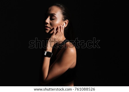 Close up portrait of a pretty asian woman dressed in sportswear listening to music with mobile phone isolated over black background #761088526