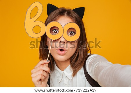 Close up portrait of a pretty teenage schoolgirl in uniform with backpack taking a selfie while standing and holding paper mask isolated over orange background