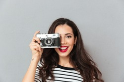 Close up portrait of a pretty woman taking a photo with a vintage camera isolated over gray background