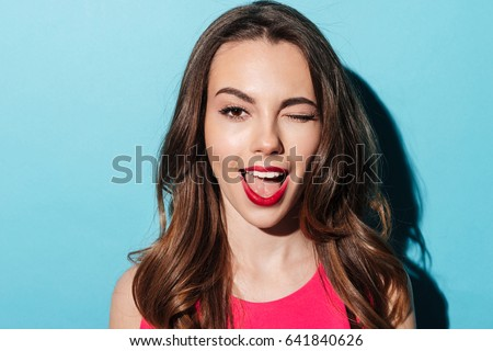 Close up portrait of a pretty young woman winking isolated over blue background