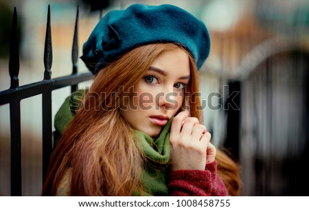 Close up portrait of a redhead  Beautiful girl in a green scarf and blue hat standing on colorful background. Art work of romantic woman .Pretty tenderness model looking at camera.
