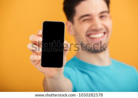 Close up portrait of a satisfied young man in t-shirt showing blank screen mobile phone isolated over yellow background