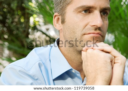 Close up portrait of a senior businessman sitting in a city park and holding his hands together under his chin, being thoughtful, outdoors.