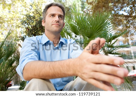 Close up portrait of a senior businessman sitting in a city park and holding his hands together, being thoughtful, outdoors.