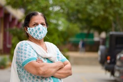 Close up Portrait of a senior Indian lady wearing surgical cotton mask matching with her salwar kameez to protect herself from Corona Virus (COVID-19) pandemic, hands folded / crossed in India