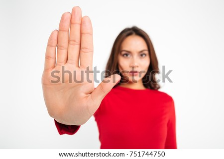 Close up portrait of a serious young asian woman showing stop gesture with hand isolated over white background