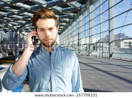 Close up portrait of a serious young man talking on mobile phone inside building