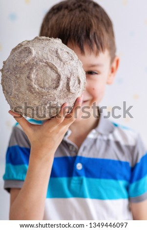 Close-up portrait of a seven-year-old boy with a papier-mâché moon layout. Half of the face is ravaged by the moon. Cosmonautics Day. Pre-school science education. Moon craters Foto d'archivio ©