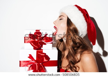 Close up portrait of a sexy young beautiful woman in red xmas hat licking present boxes isolated over white background