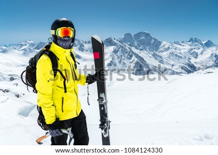 Close-up portrait of a skier wearing a protective helmet and glasses. A mask and scarf with an ice ax in his hands next to skis on the snow-capped mountains of the Caucasus. Skiing