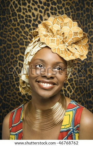 Close-up portrait of a smiling African American woman wearing traditional African clothing in front of a patterned wall. Vertical format.