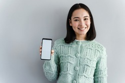 Close up portrait of a smiling asian woman showing a blank screen of a mobile phone. Young woman standing isolated over gray background.