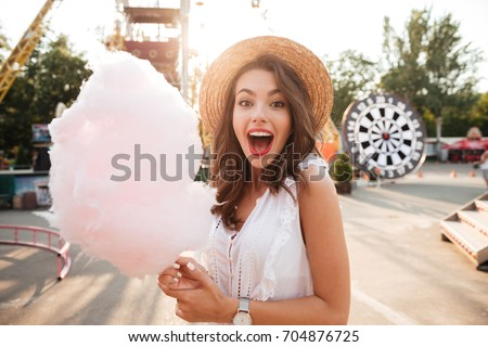 Close up portrait of a smiling excited girl holding cotton candy at amusement park