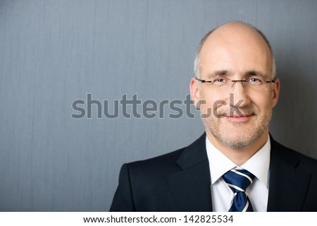 Close-up portrait of a smiling friendly mature balding businessman, wearing a suit and a necktie, leaning against a gray wall with copy-space