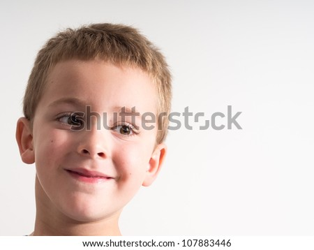 Close-up portrait of a smiling little boy isolated on white background