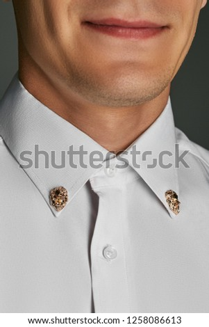Close up portrait of a smiling man posing on grey background. There are lips, chin and neck seen. The man is wearing a white button-up shirt with 2 golden collar-studs in the shape of a leonine head.