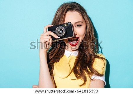 Photo of  Close up portrait of a smiling pretty girl in dress taking photo on a retro camera isolated over blue background