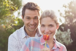 Close-up portrait of a smiling young couple holding a flower in the park