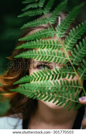 Close Up Portrait Of a Smiling Young Happy Beauty Red Hair Girl Holding Leaf Up To Face In Summer Park Forest