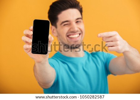 Close up portrait of a smiling young man in t-shirt pointing finger at blank screen mobile phone isolated over yellow background #1050282587
